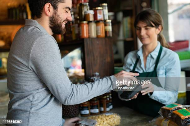 handsome male customer at a delicatessen buying products making a contactless payment with smartphone - local produce stock pictures, royalty-free photos & images