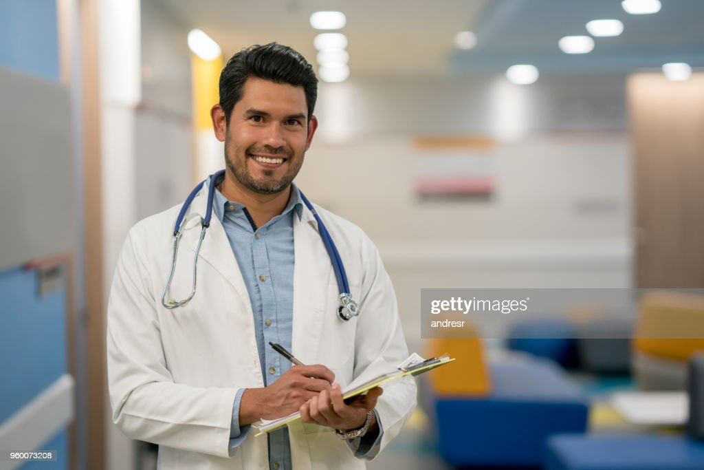 Handsome male doctor writing on a medical chart while looking at camera smiling very happy : Stock Photo