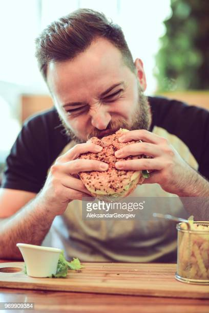 handsome male eating a cheeseburger in fast food restaurant - biting stock pictures, royalty-free photos & images