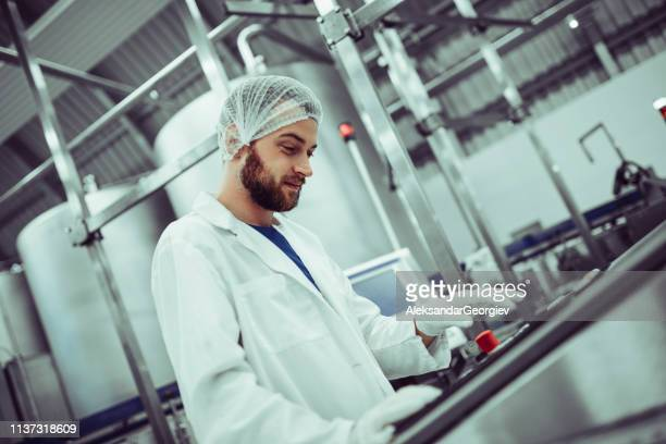 Handsome Male Examining Bottles In Production Line