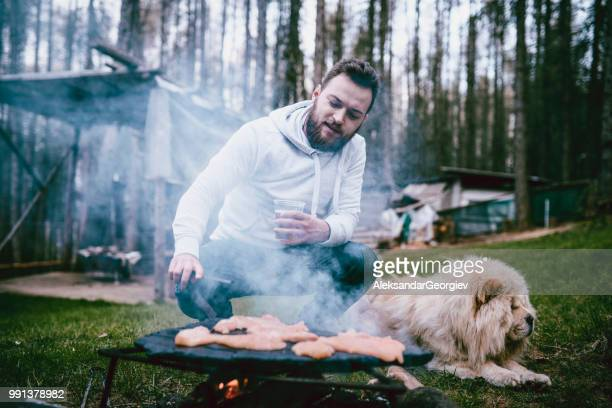 Handsome Male Making Barbecue While Pet Dog Rests Next To Him