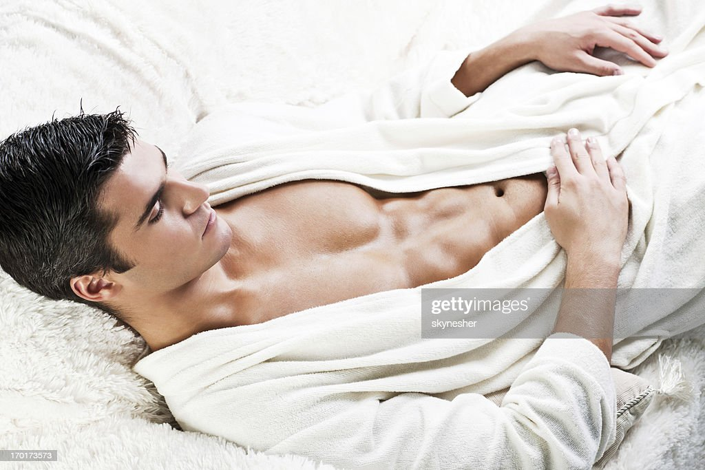 Handsome male model lying in the bed wearing bathrobe. : Stock Photo