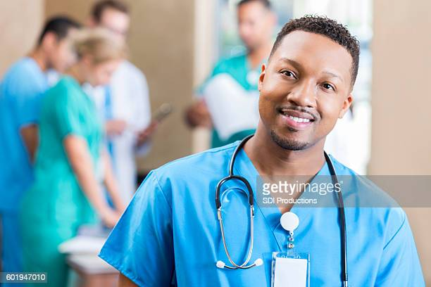 Handsome male nurse attends staff meeting