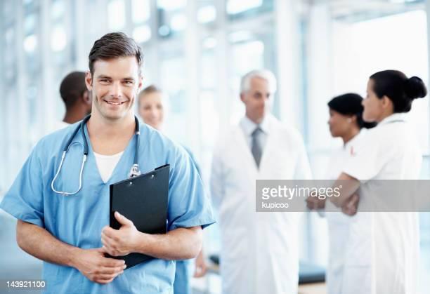 bonito e enfermeiro com equipe médica em segundo plano - enfermeiros - fotografias e filmes do acervo