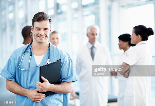Hombre atractivo con el equipo médico enfermera en el fondo