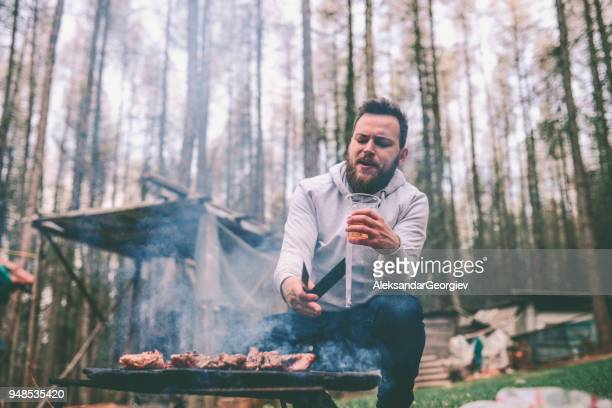 handsome male preparing barbecue and drink beer on family picnic - snag tree stock pictures, royalty-free photos & images