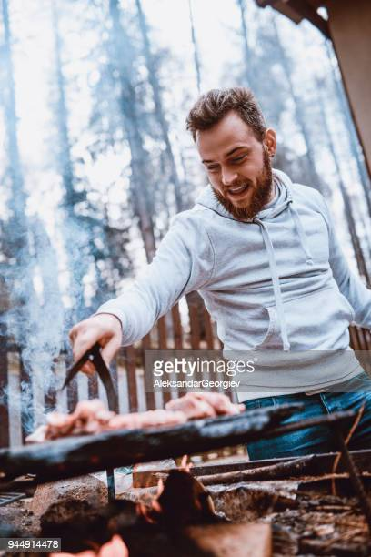 handsome male preparing barbecue on family picnic - snag tree stock pictures, royalty-free photos & images