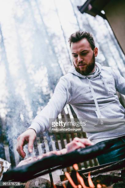 handsome male putting meat to roast on barbecue - snag tree stock pictures, royalty-free photos & images