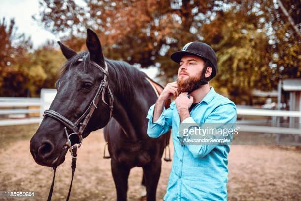 macho considerável que põr sobre o capacete para montar o cavalo - evento equestre - fotografias e filmes do acervo