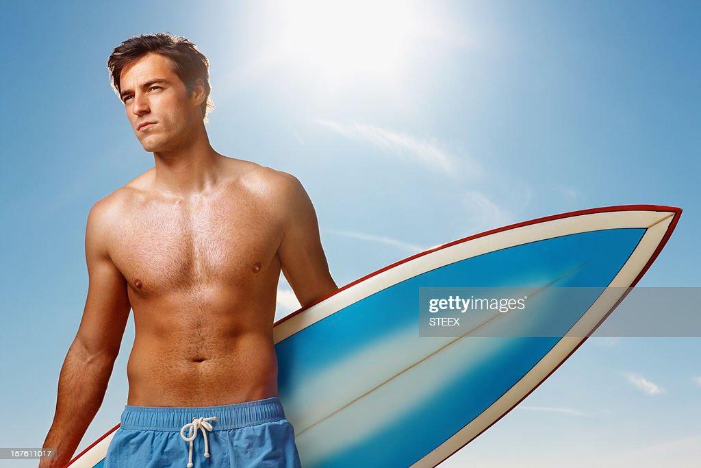 Gut aussehender Mann stehend am Strand mit Surfbrett : Stock-Foto