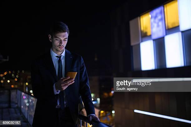 Bel homme parlant sur téléphone portable sur balcon