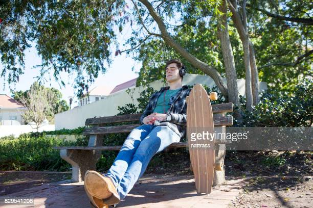 Handsome male teenage skater relaxing on the park bench