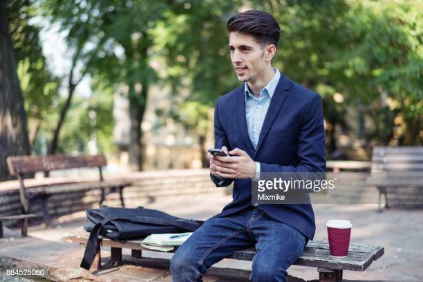 Handsome male texting on his mobile phone