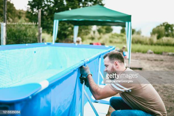 Handsome Male Worker Installing Pool Support System
