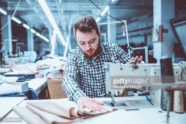 Handsome Male Worker Sewing Materials Together In Textile Factory