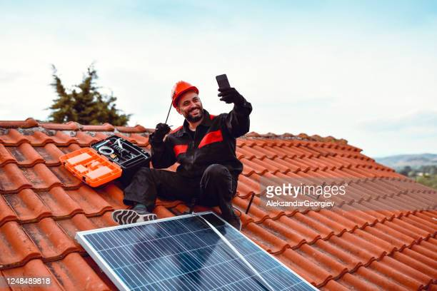 handsome male worker taking selfie on house roof with solar panel - roof tile stock pictures, royalty-free photos & images