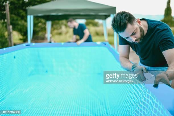 Handsome Male Workers Adjusting Pool