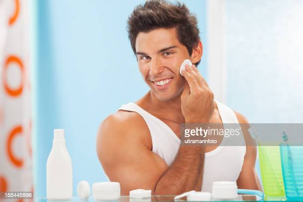 Handsome man applying cleaning lotion