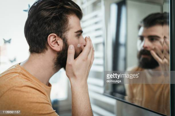 handsome man applying face cream in the bathroom - body care stock pictures, royalty-free photos & images
