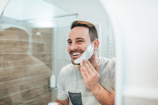 Handsome man applying shaving cream, reflection in the mirror image. 1086347186