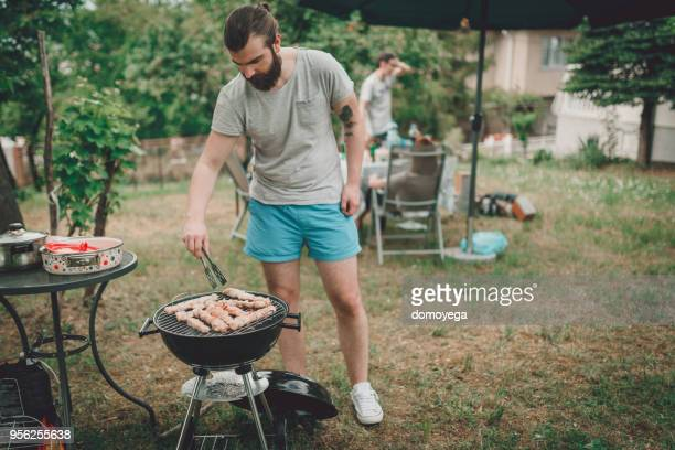 Handsome man barbequing outdoors