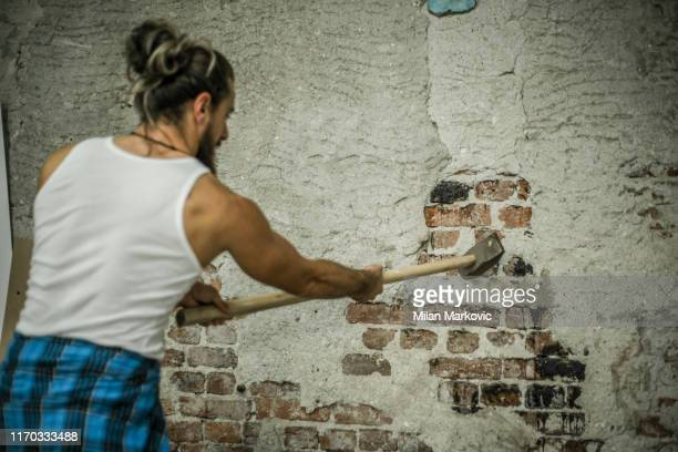 ハンサムな男はハンマーで壁を壊す - 金づち ストックフォトと画像