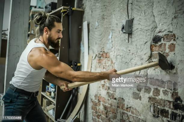 ハンサムな男はハンマーで壁を壊す - 破壊 ストックフォトと画像