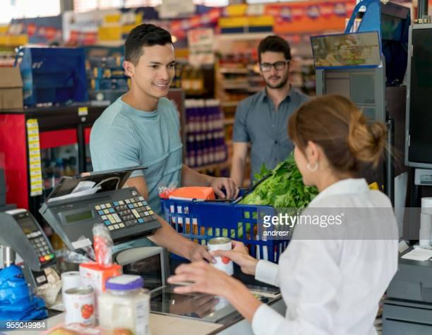Gut aussehender Mann, Kauf von Lebensmitteln auf ein Lebensmittelgeschäft und ein anderer Kunde zur Kasse im Hintergrund warten