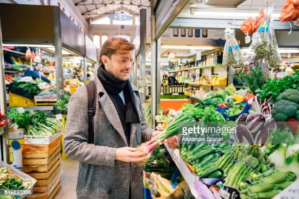 handsome man buying groceries at a market - expatriate stock pictures, royalty-free photos & images
