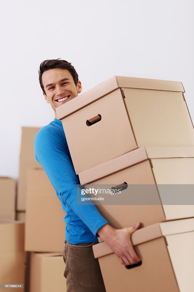 Handsome man carrying stack of boxes : Stock Photo