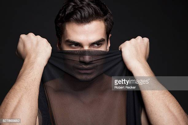 Handsome man covers face with a veil