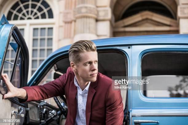 handsome man disembarking vintage car - ワインレッド ストックフォトと画像