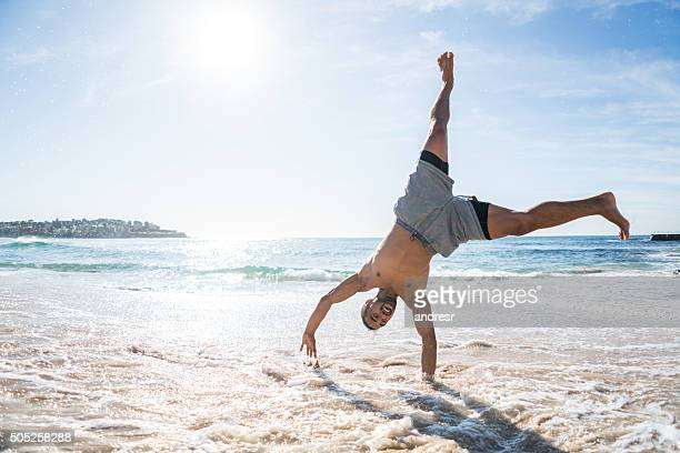 Handsome man doing a cartwheel at the beach