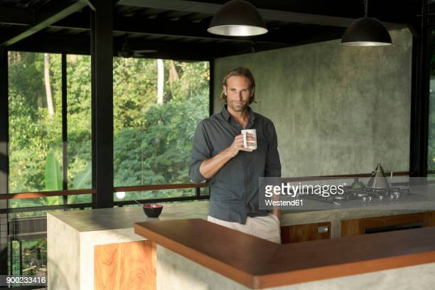 Handsome man drinking coffee in modern design kitchen with glass facade surrounded by lush tropical garden