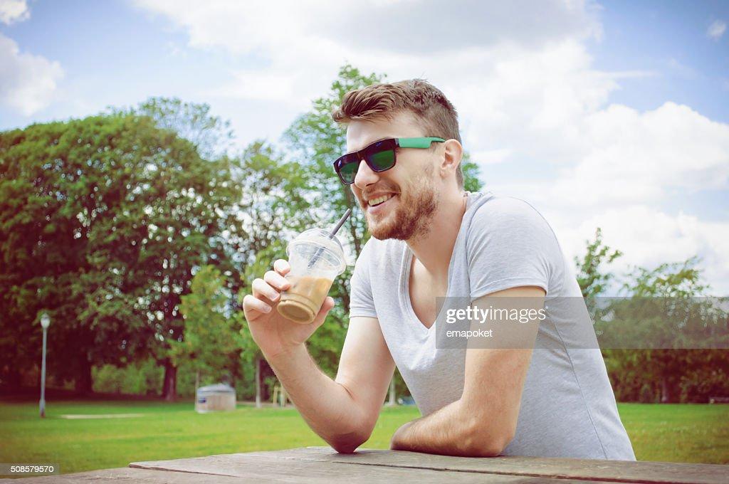 Gut aussehender Mann trinkt Kaffee im park : Stock-Foto