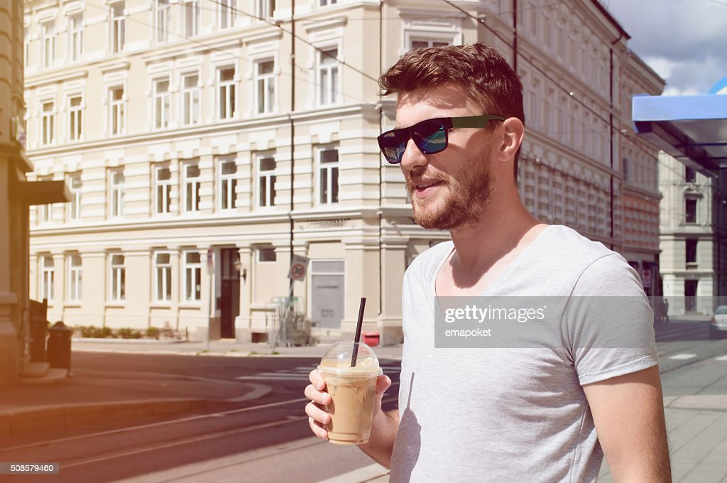 Handsome man drinking coffee on street : Stockfoto