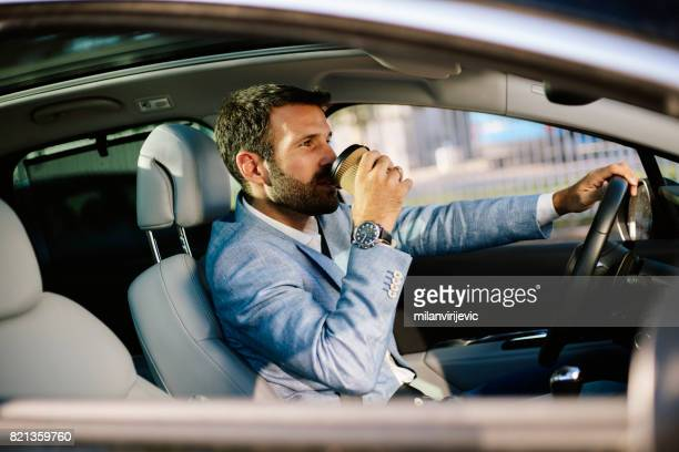 Handsome man drinking coffee while driving