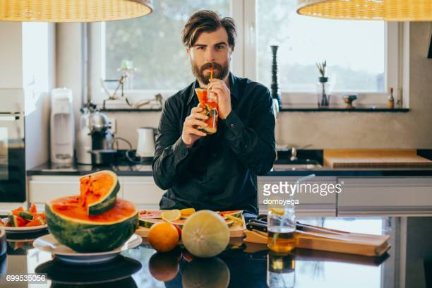 Handsome man drinking watermelon juice in the kitchen