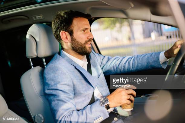 Handsome man driving a car and drinking coffee