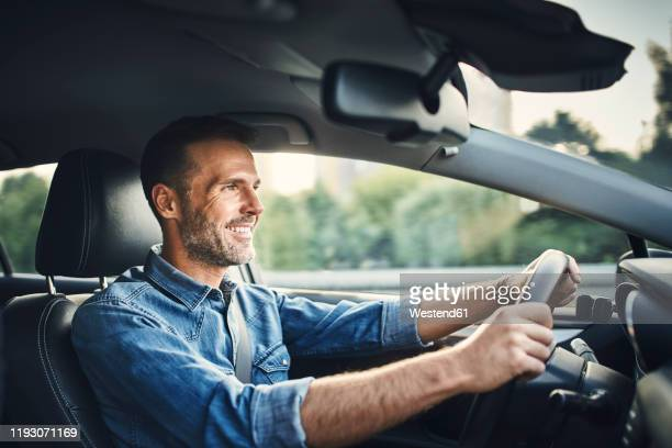 handsome man driving a car - driver stock pictures, royalty-free photos & images
