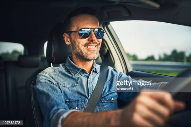 handsome man driving a car - sunglasses stock pictures, royalty-free photos & images