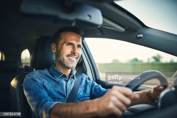 handsome man driving a car - driving stock pictures, royalty-free photos & images