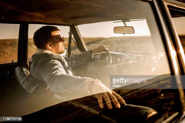handsome man driving car in sunset - vintage car stock pictures, royalty-free photos & images