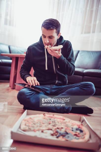 Gut aussehender Mann Pizza essen und auf seine digitale Tablet zu Hause im Internet surfen