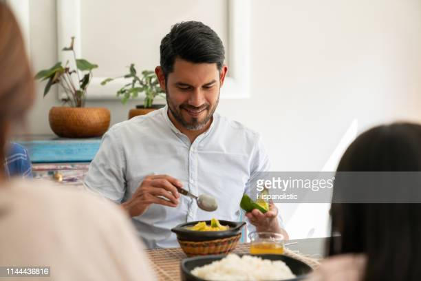 Handsome man enjoying a delicious ajiaco with family at home