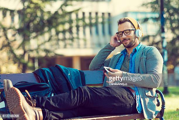 handsome man enjoying after work sitting on a bench