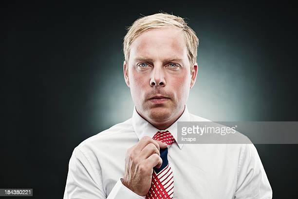 Handsome man fixing his tie
