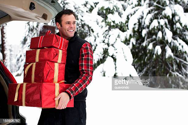 Beautiful Man Carrying Christmas Gifts from Trunk on Snowy Day