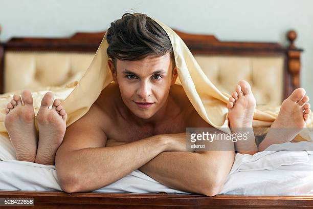 handsome man in bed with two women - pretty toes and feet stock photos and pictures