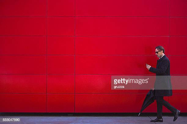 handsome man in black walking beside the red wall - red stock pictures, royalty-free photos & images